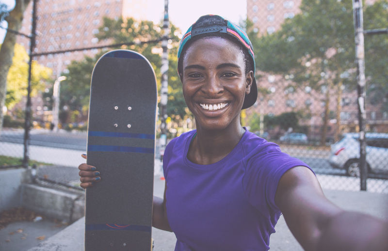 Portrait of smiling young woman holding skateboard standing in city