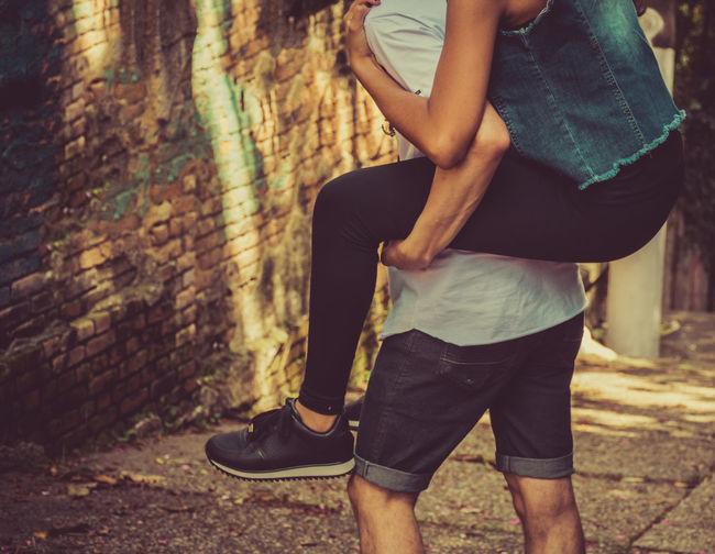 Midsection Of Boyfriend Piggybacking Girlfriend Outdoors
