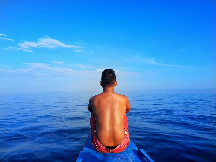 Rear View Of Shirtless Man On Boat In Sea