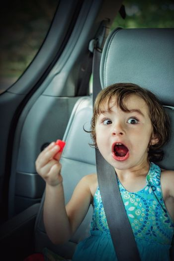 Portrait of cute girl making face while holding candy in car