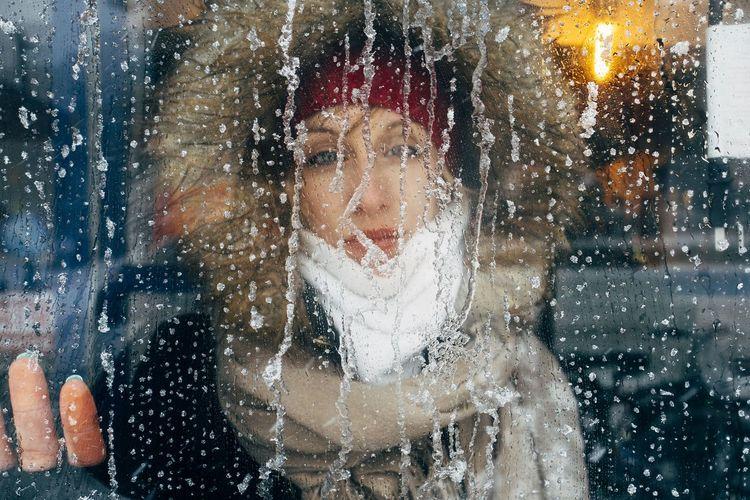 Portrait Of Woman Looking Through Frozen Window