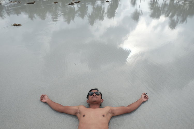High angle view of man with arms outstretched lying on beach