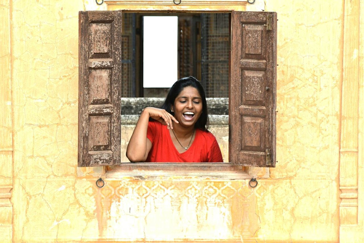 door, window, architecture, mid adult, one mid adult woman only, one person, doorway, front view, portrait, looking at camera, built structure, smiling, building exterior, day, photography themes, one woman only, adults only, curtain, indoors, cheerful, adult, headshot, photographing, real people, selfie, only women, wireless technology, people, photo messaging