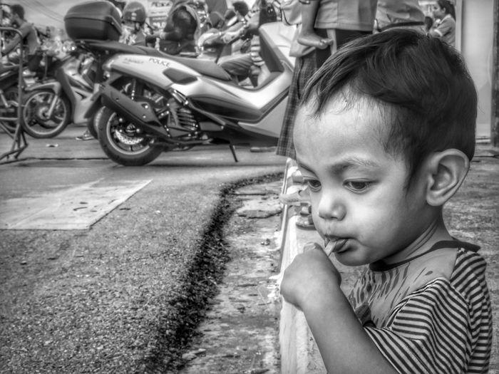 Cute boy eating lollipop while looking down on street