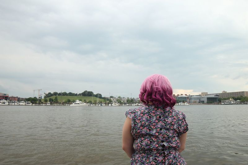 Mid shot of woman with pink hair and floral dress looking out to Baltimore harbor Tranquil Creative Peaceful Baltimore Maryland Inner Harbor Rear View Sky Water Cloud - Sky One Person Women Lifestyles Leisure Activity Real People Adult Nature Casual Clothing Standing Hairstyle Built Structure Architecture Day Hair Outdoors Dyed Hair