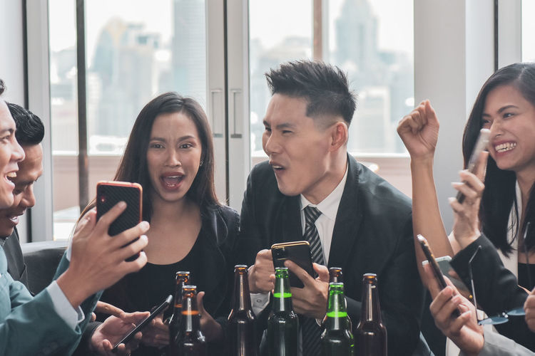 Colleagues using smart phone at restaurant