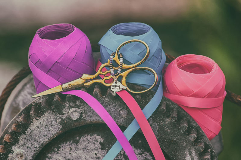 High angle view of multi colored ribbons and scissors.