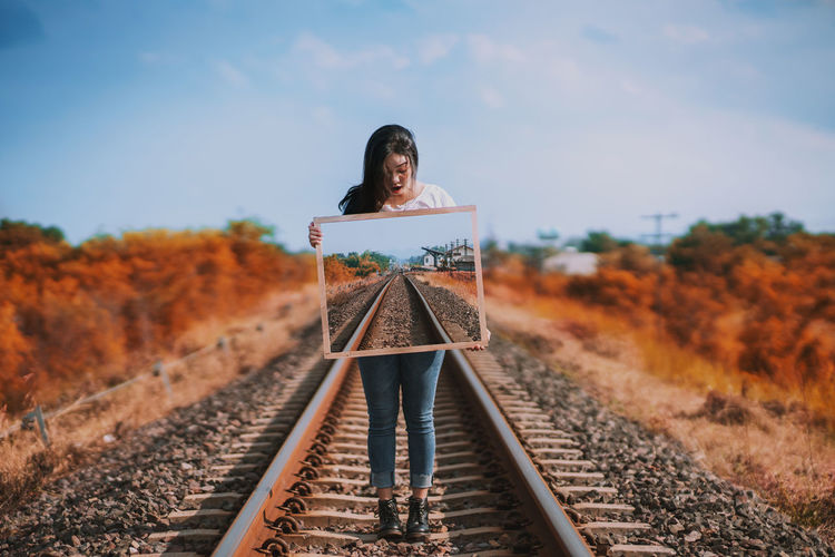 Full length of woman standing on railroad track