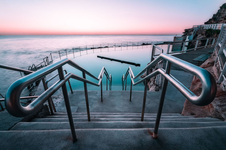 Metallic structure by swimming pool against sky during sunset