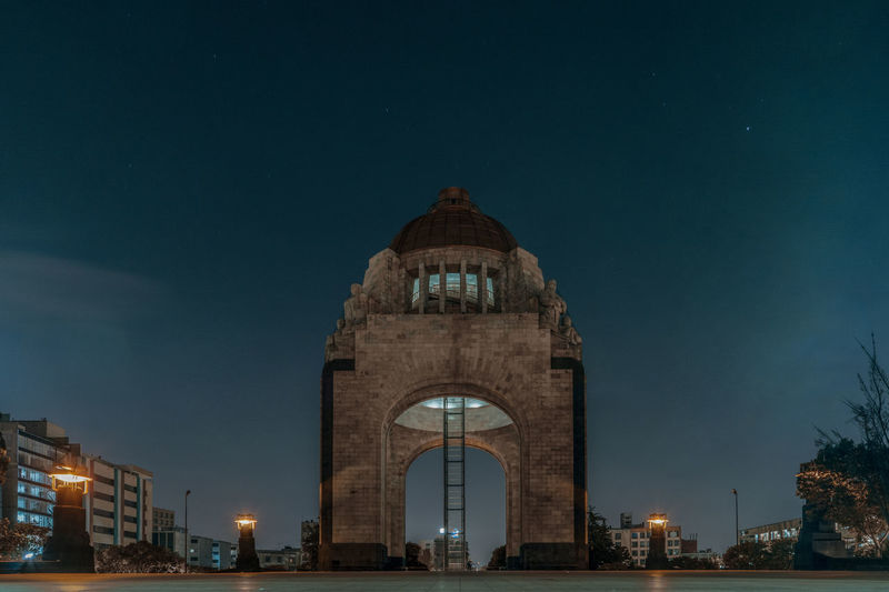 Low angle view of revolution monument against sky at dusk in city
