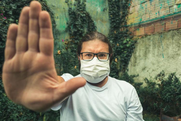 Portrait of man wearing flu mask gesturing stop outdoors