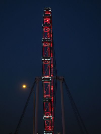 Low angle view of illuminated crane against sky at night