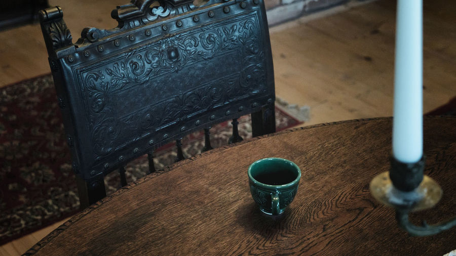 Close up view of artisanal tea cup on wooden table with old vintage wood royal armchair