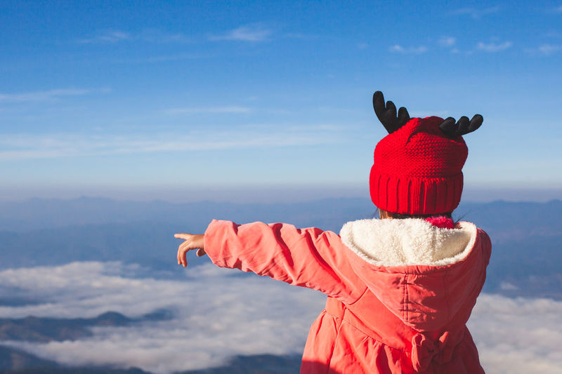 Girl In Warm Clothing Pointing Against Blue Sky During Winter