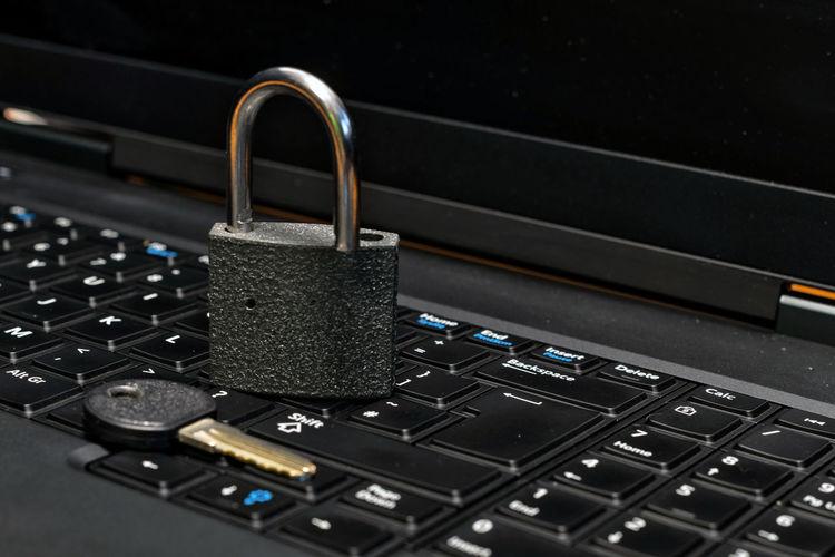 Close-up of padlock and key on laptop keyboard