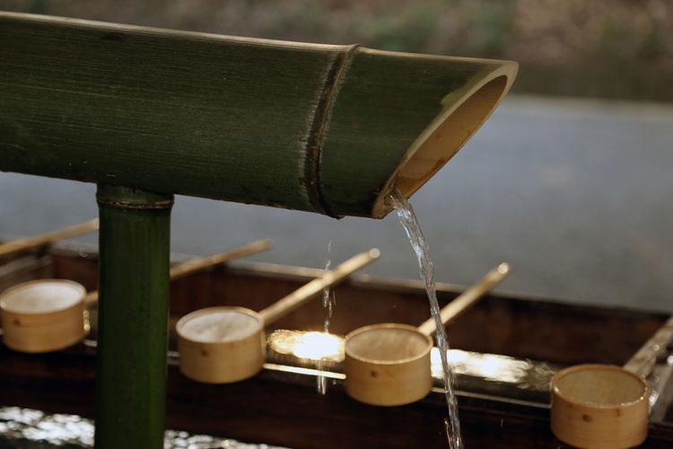 Close-up of water falling from bamboo dipper at shrine