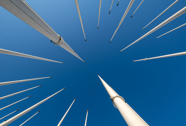 Low angle view of flag poles against clear blue sky