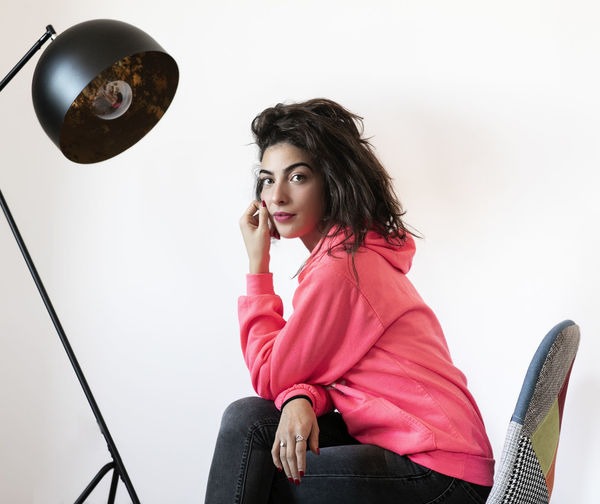 Portrait Of Young Woman Sitting On Chair By Floor Lamp Against White Background