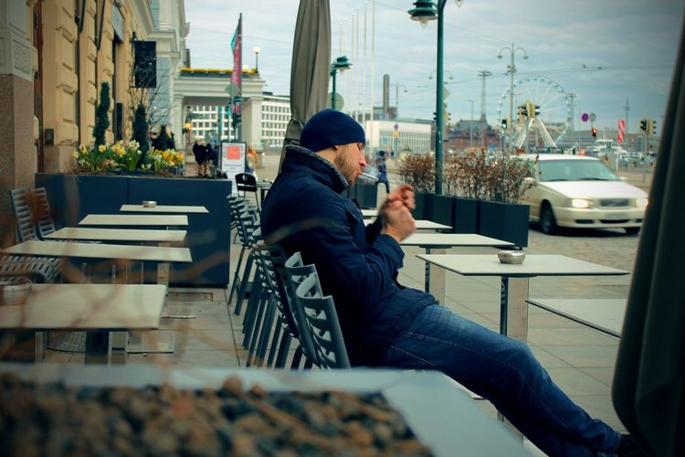 Architecture Built Structure Casual Clothing City City Life Cityscape Day Leisure Activity Lifestyles Modern Relaxation Sitting Sky The Street Photographer - 2016 EyeEm Awards Men Smoking Helsinki Cafe Sitting Outside