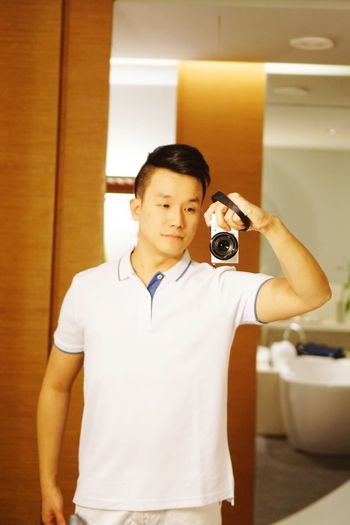 Mid adult man photographing with camera while standing at home