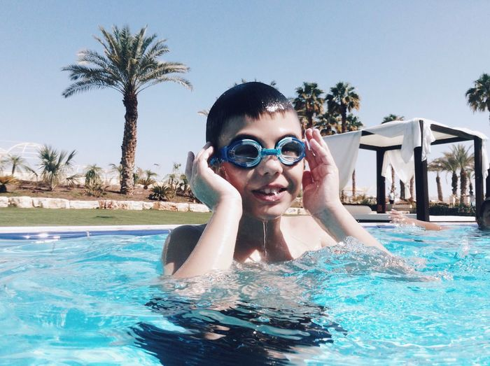 Swimming Pool Water Leisure Activity Palm Tree Sommergefühle Looking At Camera Outdoors Tree Front View Day Portrait Elementary Age Lifestyles Childhood Swimming Sky One Person Nature Ipod Shotonipod מייאייפוד מייגיא מייים Live For The Story