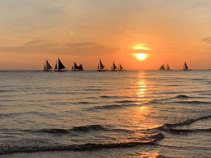 Sailboats sailing in sea against sky during sunset