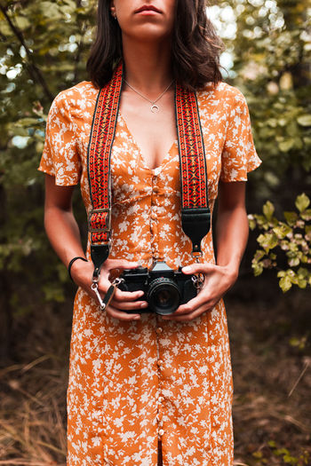 Midsection of woman holding camera standing in forest