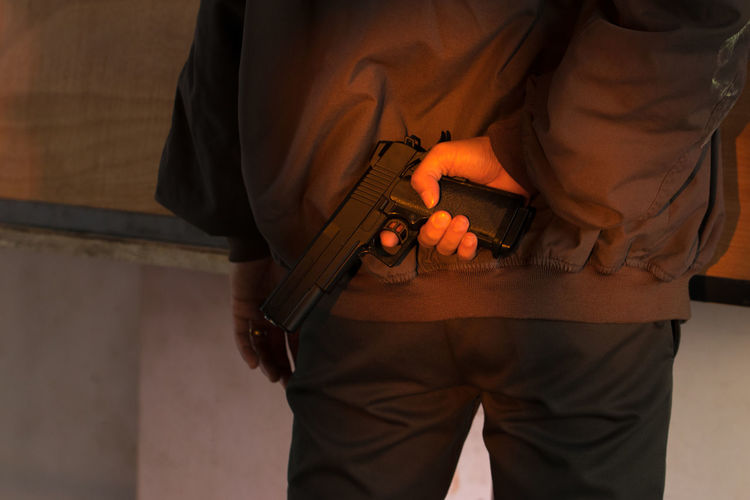 Midsection of man holding gun while standing indoors