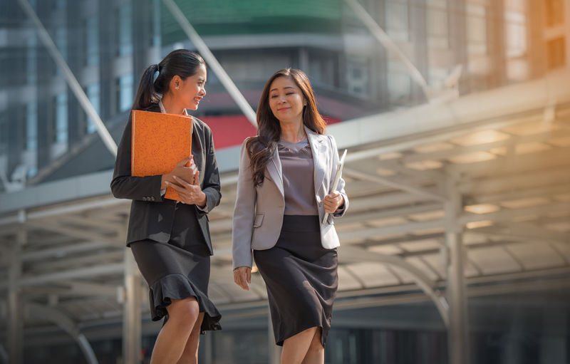 Two business women walk to work. Architecture Building Exterior Built Structure City Day Focus On Foreground Friendship Lifestyles Outdoors Real People Two People Walking Well-dressed Wireless Technology Women Young Adult Young Women