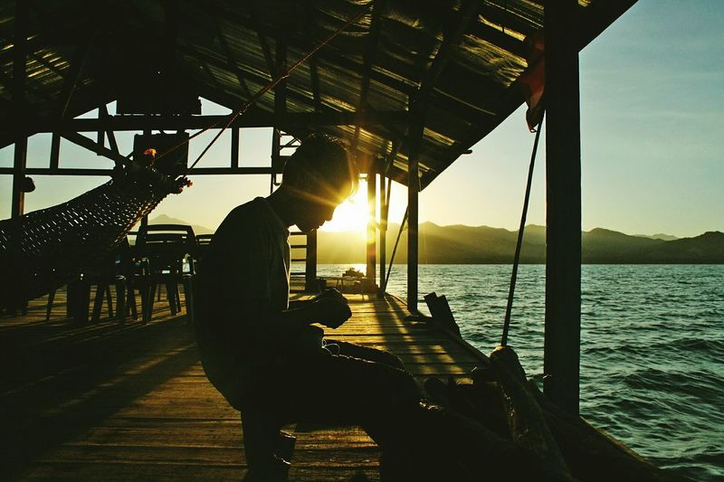 A fisherman prepares his bira-bira on sundown, a string device with green threads tied to it used to lure fish for catching. Puerto Princesa, Palawan, Philippines. The Traveler - 2015 EyeEm Awards Travel People Traveling Portrait Sunset_collection Light And Shadow Silhouettes Sunset Silhouettes Snapshots Of Life The 2015 EyeEm Awards Finalists