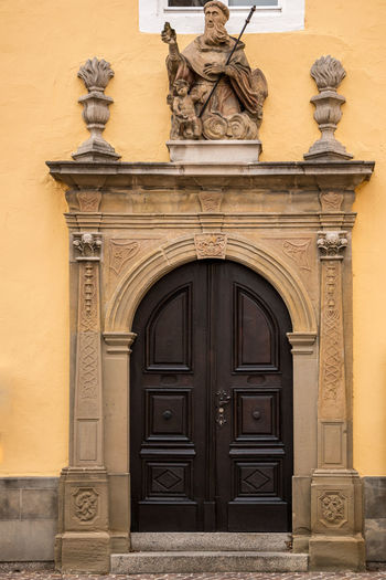 Old door of a historical building with statues and coats of arms made of stone Architecture Entrance Building Exterior Art And Craft Built Structure Sculpture Representation Door Arch Craft Human Representation No People The Past History Creativity Day Ornate Statue Closed Male Likeness Outdoors Bas Relief Carving
