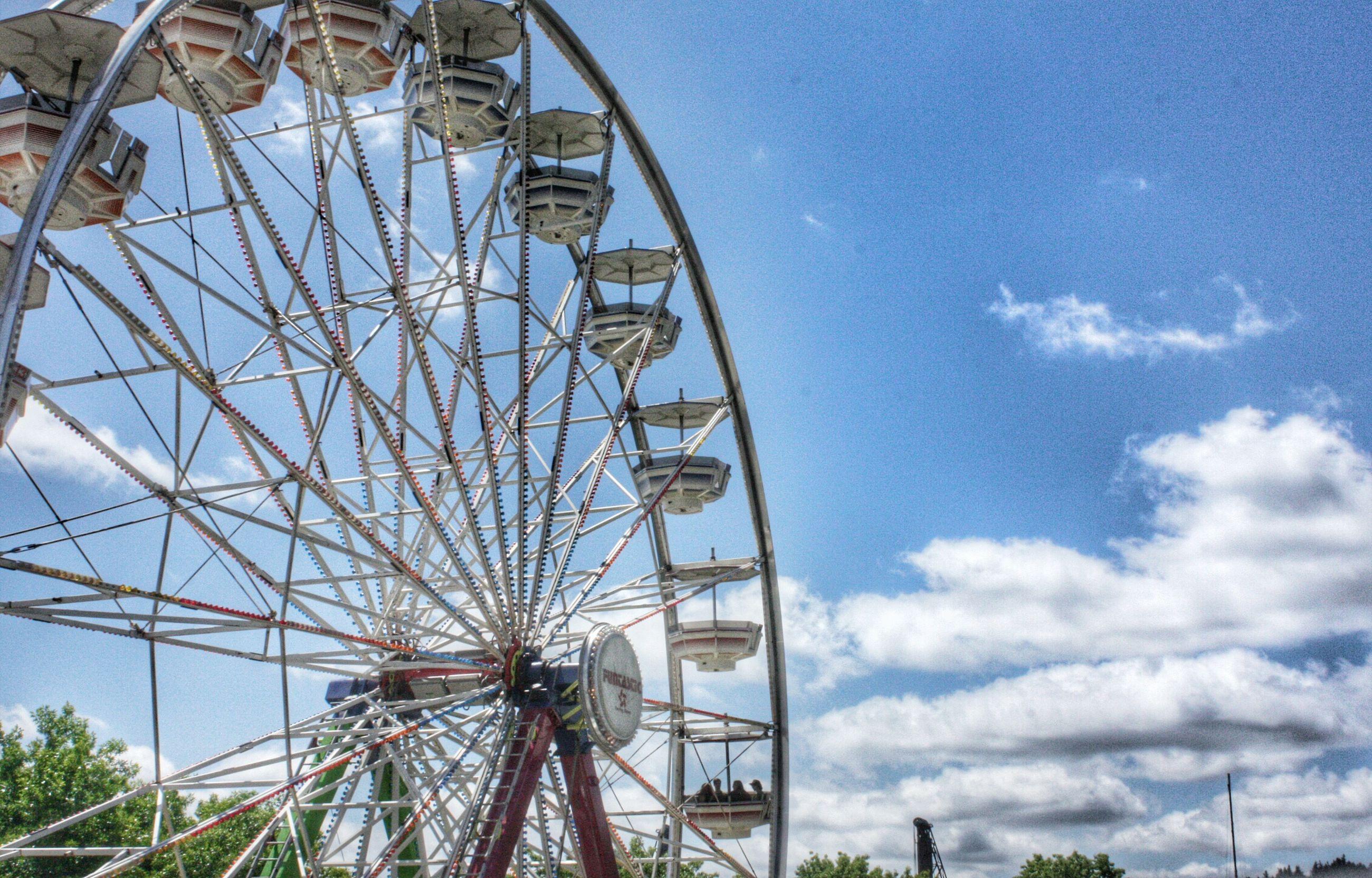 amusement park, ferris wheel, amusement park ride, low angle view, arts culture and entertainment, sky, cloud - sky, blue, built structure, large, cloud, big wheel, fairground ride, metal, fun, day, fairground, outdoors, cloudy, architecture