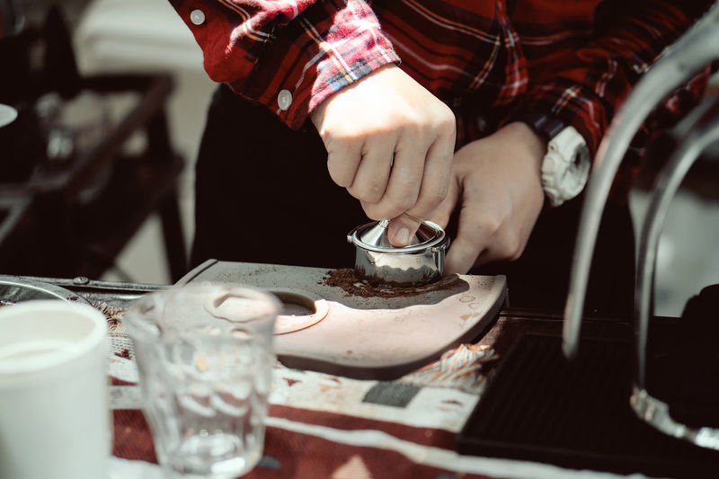 Midsection of man playing with drink on table