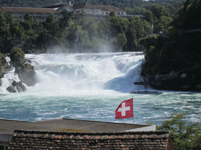 The Rhine Falls near Schaffhausen (Neuhausen am Rheinfall), in northern Switzerland, is the largest plain waterfall in Europe. Schloss Laufen sits within touching distance of this natural wonder; so close that you can feel the spray on your face. Visitors can walk around the falls or get a close-up feel of the water's force by taking a boat trip. Rhine Falls, Laufen-Uhwiesen, Switzerland. http://pics.travelnotes.org/ Michel Guntern Natural Beauty Rheinfall Rhine Falls Sightseeing Tourist Attraction  Tourists Travel Travel Photography Boat Flag Motion Nature Outdoors River Scenics Schaffhausen Spray Swiss Flag Switzerland Tourism Travel Pics Water Waterfall Waterfalls