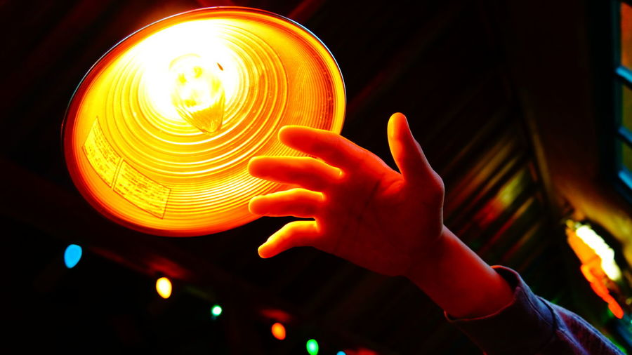 Cropped Image Of Hand By Illuminated Pendant Light At Home