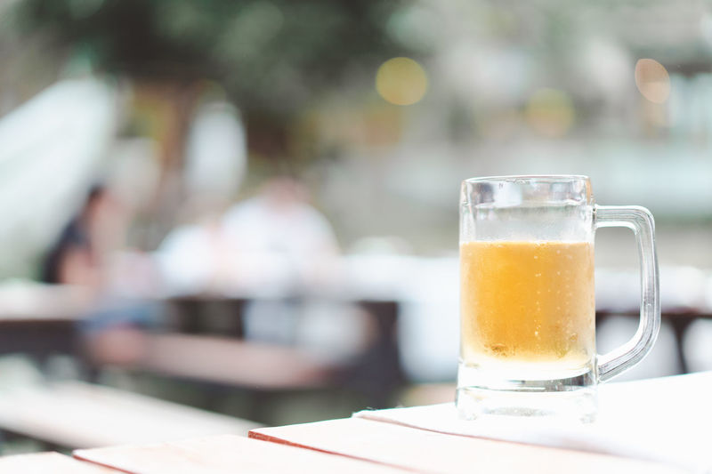 beer mug at restaurant with blurred couple dinner together, retro tone Alcohol Bar Beer Beverage Bokeh Bright Celebrate Cheers Chill Cold Couple Day Dinner Drink Focus Fresh Friends Glass Golden Happy Light Mug Party People Refreshment Relax Restaurant Selective Together Yellow