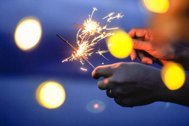 Cropped Hands Of Person Holding Illuminated Sparklers At Night