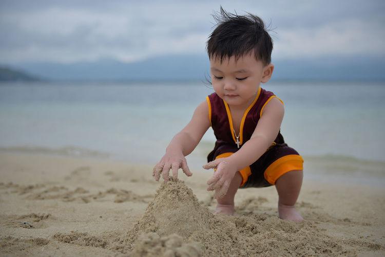 Boy playing on beach against sky