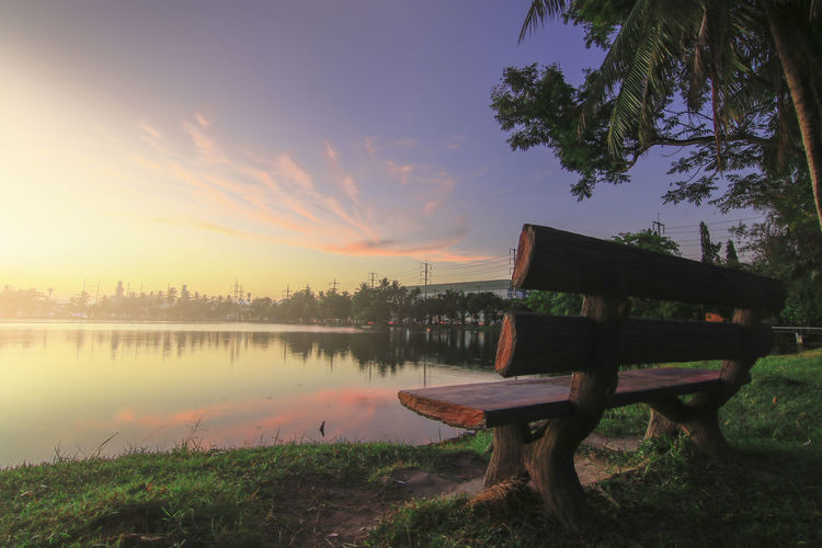 Bench by lake against sky during sunset