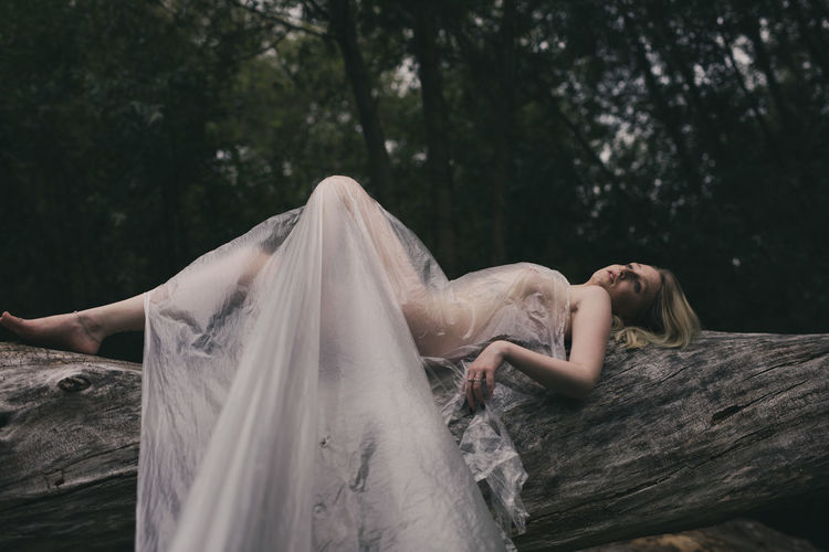 Young naked woman lying down on tree trunk in forest