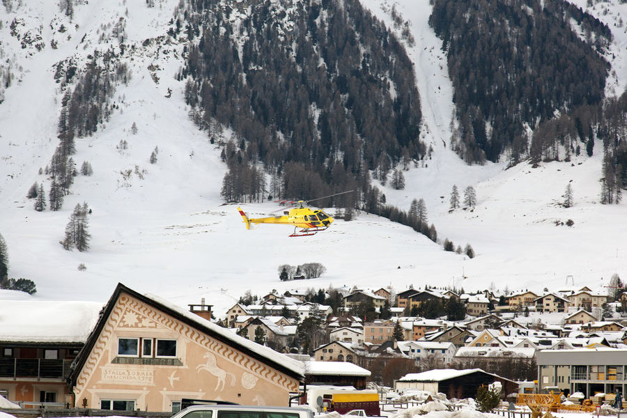 A yellow sightseeing tour helicopter flying over the cute village in the alps switzerland in winter Architecture Helicopter Holiday Home Postcard Sightseeing Transportation Travel Winter Alps Alps Austria Aviation Building Flight Flying Historic House Mountain Snow St Moritz Town Transportation Building - Type Of Building Vacation Village Winter Holiday