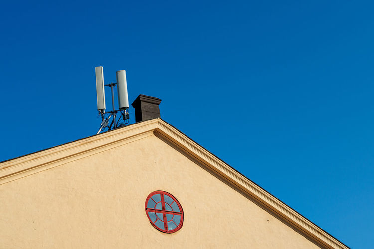 Low angle view of roof mounted telecommunications antennas