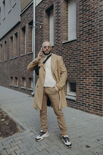 Portrait of man talking on phone while standing against building on footpath