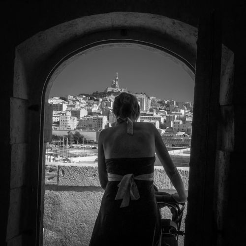 Rear View Of Woman With Baby Carriage Seen From Arch Doorway