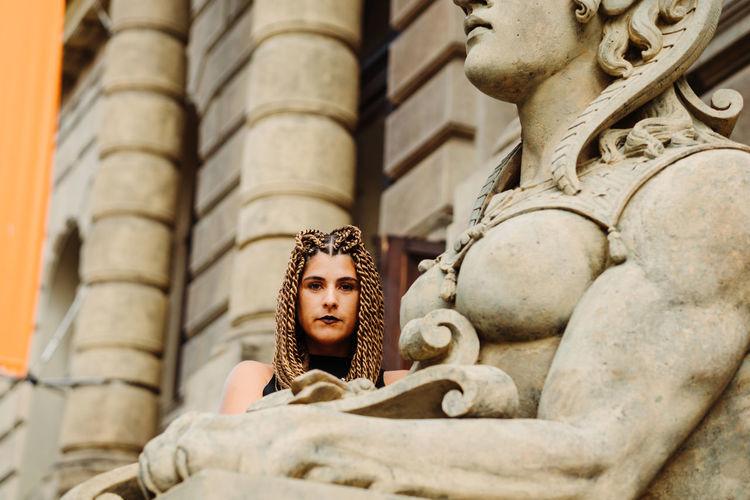 Portrait of woman by statue against historic building