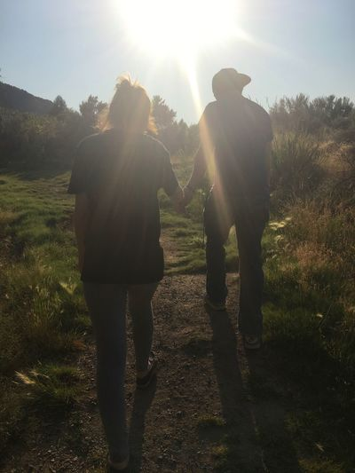 Walking Togetherness Rear View Two People Grass Love Silhouette Men Sunlight Friendship Hiking Adventure Real People Bonding Women Nature Outdoors Day Sky Adult