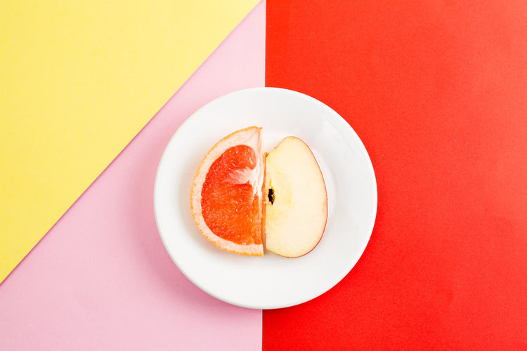 Food And Drink Food Freshness Fruit Still Life Indoors  Wellbeing Healthy Eating Table Red Plate Yellow Close-up No People Directly Above Colored Background SLICE High Angle View Ready-to-eat Pink Color Temptation