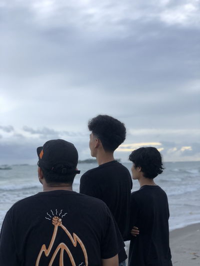 Rear view of people on beach against sky