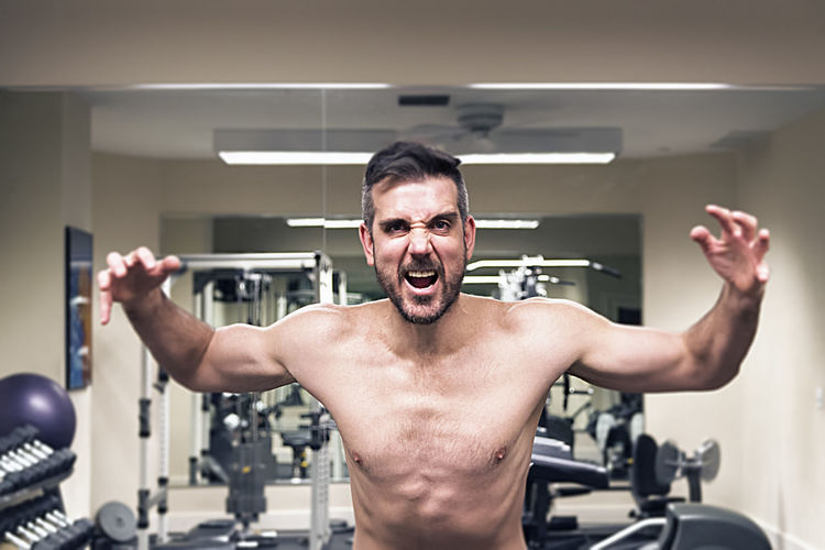 Angry determined man in a gym attacking the weights. Activity Attack Caucasian Diet Effort Exercising Fitness Front View Gym Health Club Healthy Lifestyle Lifestyles Men Muscular Build One Person Shirtless Skin Sport Sports Training Sportsman Strength Strength Training Testosterone The Human Body Weights