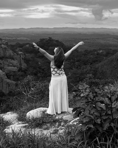 Rear view of woman with arms outstretched standing on land